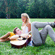 Man and woman with a guitar in the park — Stock Photo