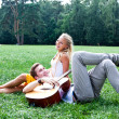 Man and woman with a guitar in the park — Stock Photo #17974593