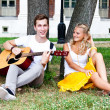 Man and woman with a guitar in the park — Stock Photo #17974611