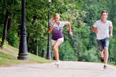 A man and a woman running in the park — Stock Photo