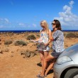 Two young women with car look at road map on a beach against sea — Stock Photo #39527937