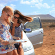 Two young women with car look at road map with mountain landscap — Stock Photo #39528043