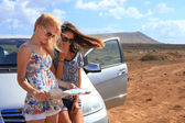 Two young women with car look at road map with mountain landscap — Stock Photo
