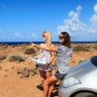 Two young women with car look at road map on a beach against sea — Stock Photo #42031155