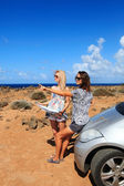Two young women with car look at road map on a beach against sea — Stock Photo