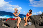 Two girls taking photo on the beach in summer holidays and vacat — Stock Photo