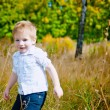 Little boy running plays in the grass — Stock Photo