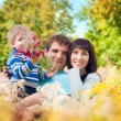 A young family with a baby on the nature in the long grass — Stock Photo