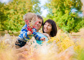 A young family with a baby outdoors in autumn — Stock Photo
