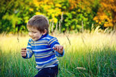 Cute little boy running around in the grass in nature — Stock Photo
