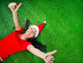 Attractive brunette girl in santa hat lying on green grass with — Stock Photo