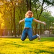 Cheerful young girl jumping in the park — Stock Photo