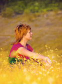 Beautiful young girl sitting in the grass at sunset — Stock Photo