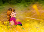 A beautiful young girl lying in the grass at sunset smiling — Stock Photo