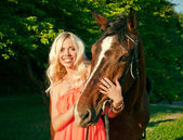 Young attractive blonde girl embraces a horse — Stock Photo