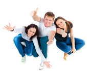 Top view of young friends sitting on the floor and showing thumb — Stock Photo