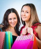 Duas linda mulher sorridente com compras em mãos — Fotografia Stock