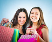 Two pretty smiling woman with purchases in hands — Stock Photo