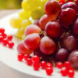 Grapes and berries in a bowl on the table — Stock Photo
