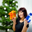 Young girl with gifts under the Christmas tree — Stock Photo