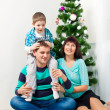 Young family having fun under the Christmas tree — Stock Photo #38293361