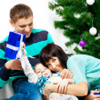 Young family having fun under the Christmas tree — Stock Photo #38293369