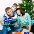 Young family having fun under the Christmas tree — Stock Photo #38293377