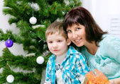 Young mother with her son near Christmas tree — Stock Photo