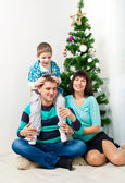Young family having fun under the Christmas tree — Stockfoto