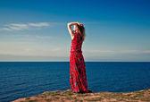 Young beautiful woman posing on sea background — Stock Photo