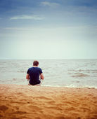 A young man sitting on the beach alone — Stock Photo