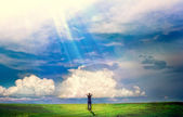 Young boy stands in a field and the sun is shining on it — Stock Photo