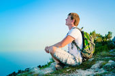 Young tourist with backpack sitting on the hill and enjoy the sc — Foto Stock