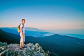 Young guy stands up in the mountains at sunset and enjoy the sea — Stock Photo