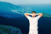 Młody zdrowy facet stojący na wzgórzu i oglądać krajobraz — Zdjęcie stockowe