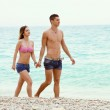 Young couple walking along the seashore — Stock Photo #48717557