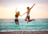 Young couple near the sea at sunset jumping — Stock Photo