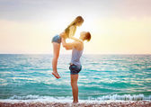 Young couple near the sea at sunset — Stock Photo