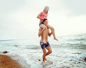 沿着海边行走的年轻夫妇,女孩坐在那家伙的 — 图库照片