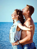 Pretty young couple embracing by the sea — Stockfoto