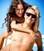 Pretty young couple having fun on the beach — Stock Photo