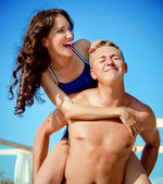 Pretty young couple having fun on the beach — Stock Photo