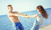 Pretty young couple having fun on the beach — Stockfoto