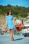 Girl walks on the quay at the sea on a background of yachts — Foto Stock