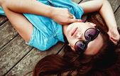 Bella ragazza sdraiata su un pavimento di legno — Foto Stock