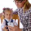 Mother and daughter with mobile phone — Stock Photo #35357249