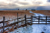 Closed road to the house fence in autumn snowfall — Stockfoto