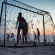 People play football on the beach at sunset - Foto Stock