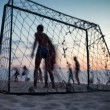 People play football on the beach at sunset - Stock Photo