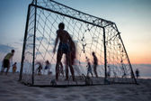 Play football on the beach at sunset — Stock Photo